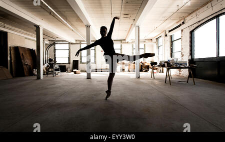 Caucasian ballet dancer performing in loft - Stock Photo