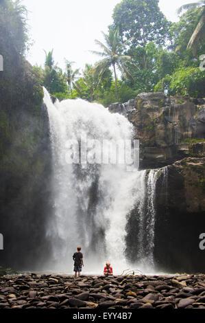 Caucasian tourists admiring waterfall in jungle - Stock Photo