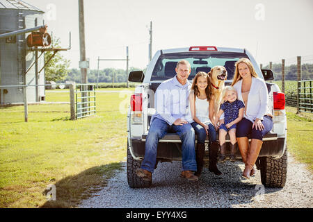Caucasian family and dog sitting in truck bed on farm - Stock Photo