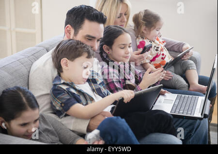 Caucasian family using technology on sofa - Stock Photo