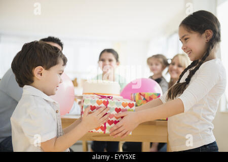 Caucasian girl giving brother birthday gift at party - Stock Photo