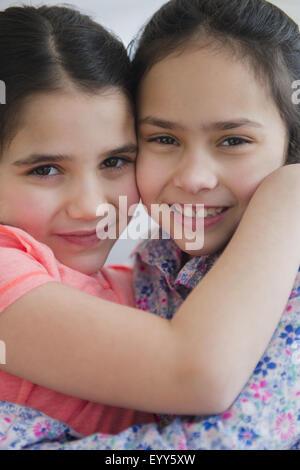 Close up of Caucasian sisters hugging - Stock Photo