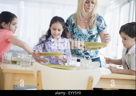 Caucasian mother and children setting table - Stock Photo