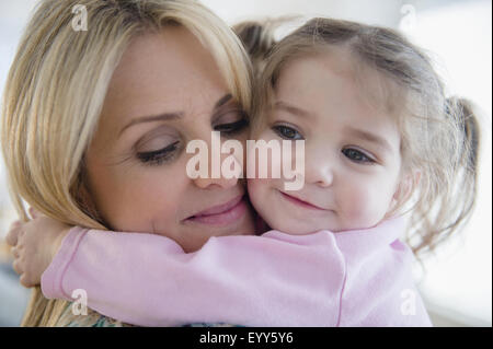 Close up of Caucasian mother hugging daughter - Stock Photo