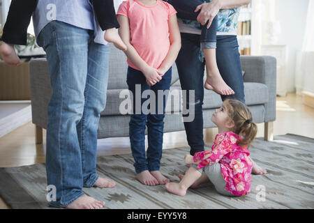 Caucasian girl sitting under family in living room - Stock Photo