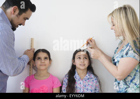 Caucasian parents measuring height of daughters on wall - Stock Photo