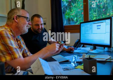 Caucasian businessmen working at desk - Stock Photo
