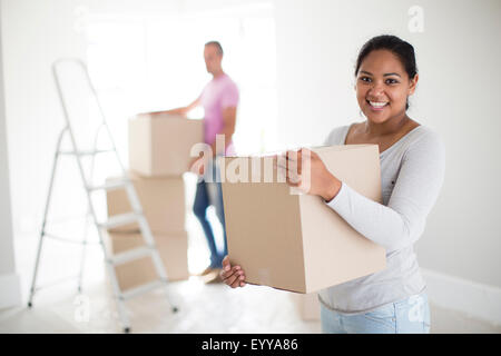 Couple holding cardboard boxes in new home - Stock Photo