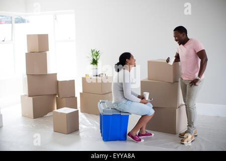 Couple with cardboard boxes in new home - Stock Photo