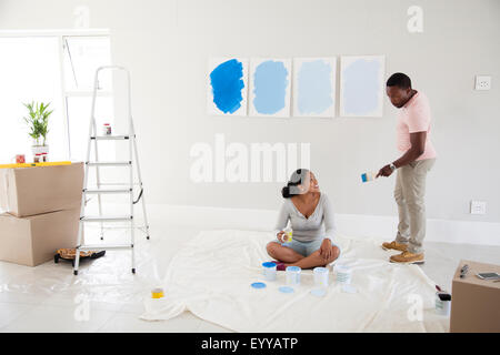 Couple examining paint samples in new home - Stock Photo