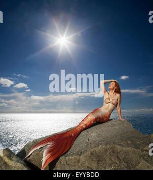 Caucasian mermaid laying on rock near ocean - Stock Photo
