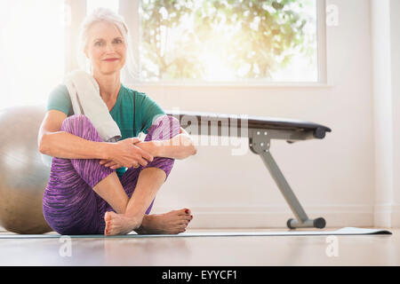 Older Caucasian woman sitting on gym floor - Stock Photo