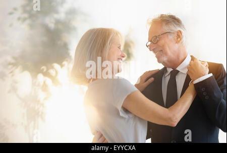 Smiling older Caucasian couple dancing - Stock Photo
