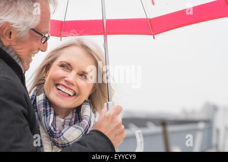 Older Caucasian couple standing under umbrella