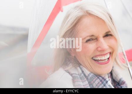 Older Caucasian woman standing under umbrella