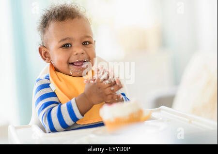 Mixed race baby boy eating in high chair - Stock Photo