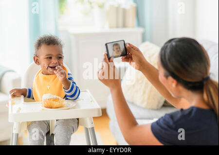 Mixed race mother photographing messy baby boy in high chair - Stock Photo