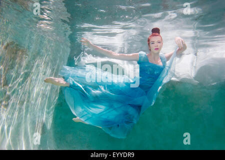 Underwater view of Caucasian woman in dress swimming in pool - Stock Photo