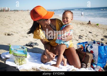 Mother and daughter playing on beach - Stock Photo