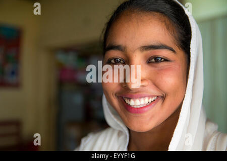 Close up of smiling girl wearing headscarf - Stock Photo