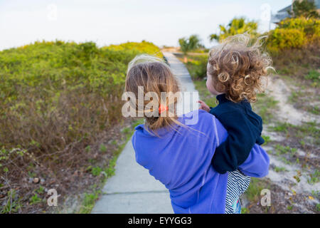 Caucasian girl carrying baby brother on wooden walkway - Stock Photo