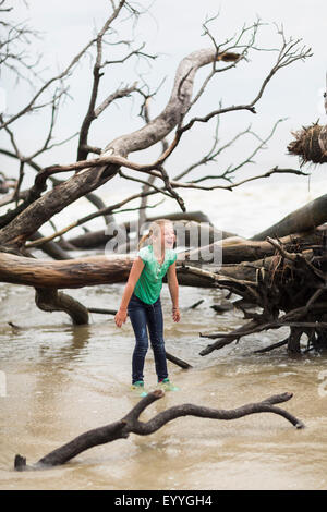 Caucasian girl playing in river near driftwood - Stock Photo