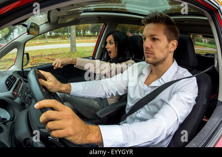young man driving car with gesticulating young woman as co-driver, Austria