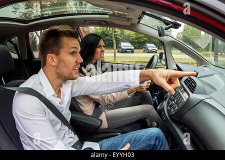 young woman driving car with gesticulating man as co-driver, Austria - Stock Photo