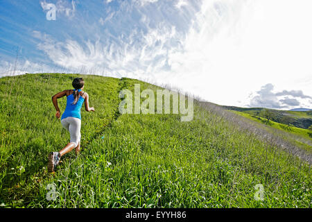 Black athlete running on rural hillside - Stock Photo