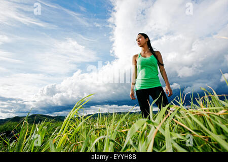 Mixed race athlete standing in rural field