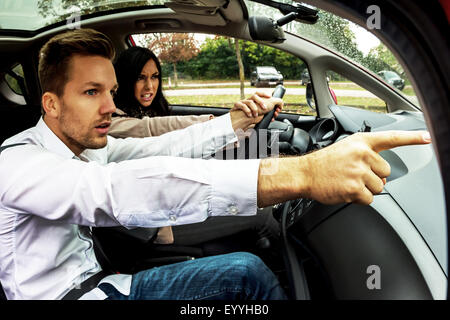 young woman driving car with gesticulating man as co-driver, Austria