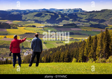 two men enjoying the view to low mountain scenery near Bruchhausen in spring, Germany, North Rhine-Westphalia, Sauerland, - Stock Photo
