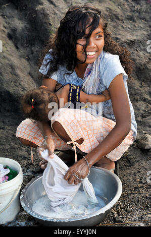 young girl with a little child on her arm doing laundry in a dish, Philippines, Luzon, Manille - Stock Photo