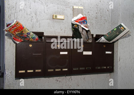 letter boxes with print media, Germany - Stock Photo