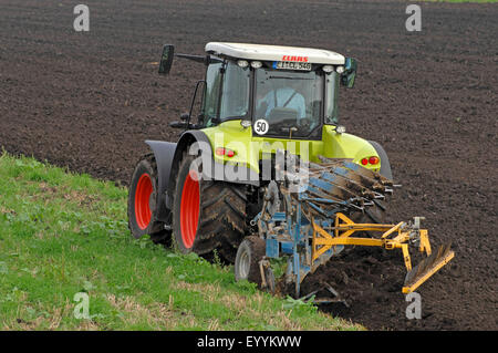 tractor ploughing a field in autumn, Germany, Bavaria - Stock Photo