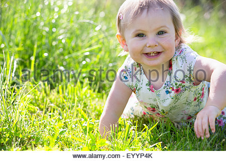 Portrait of smiling baby sitting on grass - Stock Photo