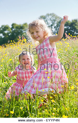 Portrait of smiling baby and young girl in matching dresses walking through wildflower flower - Stock Photo