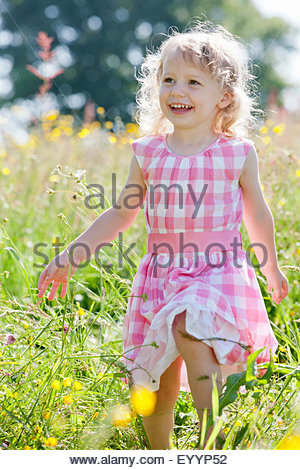 Portrait of smiling girl walking in wildflower meadow - Stock Photo