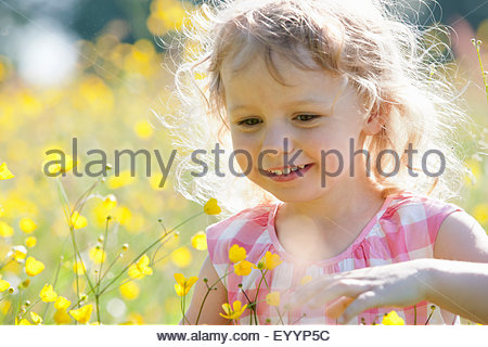 Portrait of smiling girl playing in wildflower meadow - Stock Photo