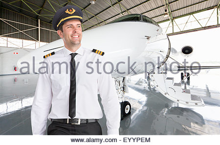 Portrait of smiling pilot standing in front of private jet - Stock Photo
