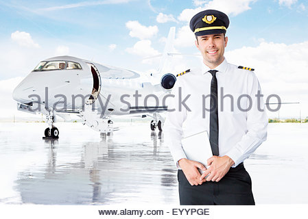 Smiling pilot standing in front of private jet - Stock Photo