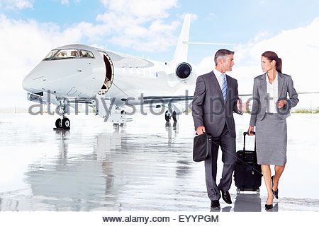 Smiling Businesswoman and Businessman walking away from private jet - Stock Photo