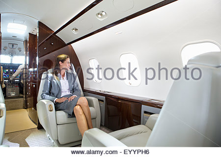 Businesswoman looking out of window on private jet - Stock Photo