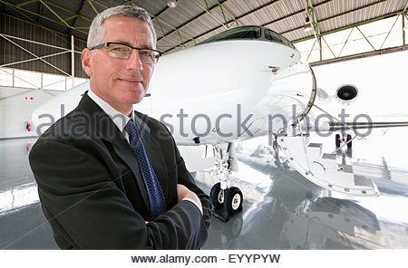 Smiling Businessman standing in front of private jet in hangar - Stock Photo