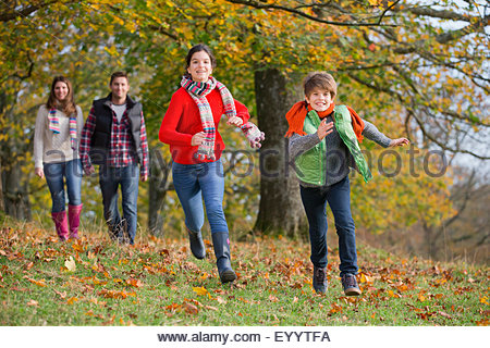 Children running in autumnal forest, with parents walking holding hands - Stock Photo