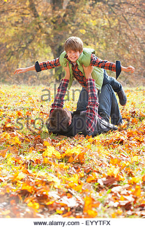 Father holding son up like a plane in autumnal park - Stock Photo