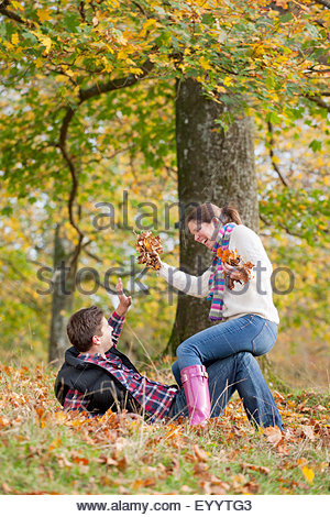 Couple playfully throwing leaves in autumnal park - Stock Photo
