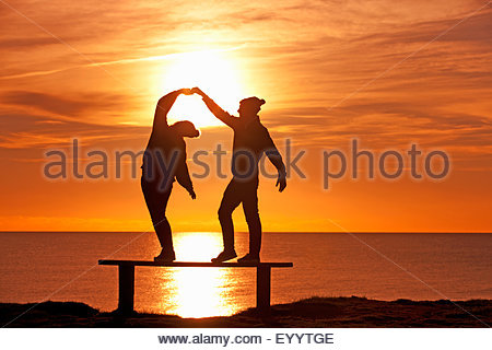 Silhouette of couple, dancing on bench, against sunset over the ocean - Stock Photo