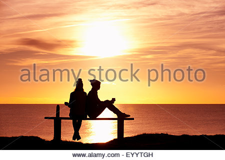 Silhouette of couple, sitting on bench and drinking tea from thermos, against sunset over the ocean - Stock Photo