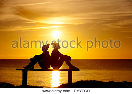 Silhouette of couple, sitting back to back on bench, against sunset over the ocean - Stock Photo
